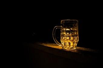 Ein Bierglas vor dunklem Hintergrund, dass beleuchtet ist
