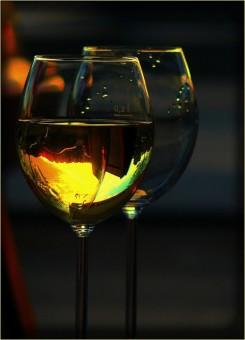 Zwei seitlich beleuchtete Weingläser mit Weißwein