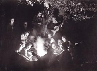 Eine Gruppe junger Wandervögel, die um ein Lagerfeuer herum sitzt, lacht und musiziert