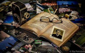 Oral History symbolisiert durch ein offenes Buch mit Foto dahinter andere Bilder und eine Kamera