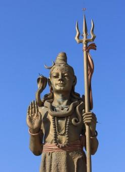 Statur der indischen Gottheit Shiva vor blauem Himmel