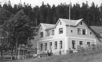 Foto des Naturfreundehaus Karlsbader Hütte in sanfter Hügellandschaft mit Wanderern im Freien