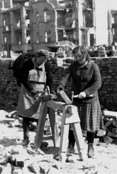 Darstellung von Trümmerfrauen, die an einer Werkbank stehen und arbeiten.