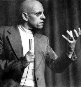 Schwarzweisß-Foto von Michael Foucault, gestikulierend bei Vortrag
